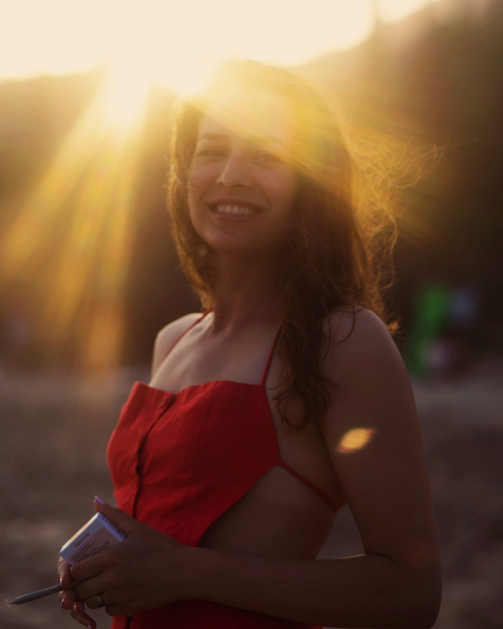 Image of Lian Bruno, a young white woman with wavy brown hair, smiling and wearing a red dress with the sun behind her.